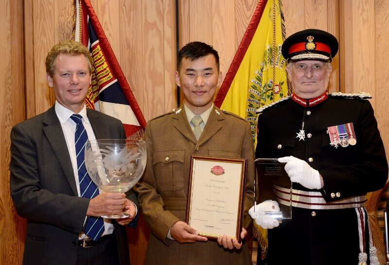 Shepherd Neame Best Reservist of the Year Award. Pictured from left to right: Mr Jonathan Neame DL, Chief Executive Shepherd Neame with the engraved trophy which he presented; Best Reservist of the Year Craftsman Madan Sherchan, 133 Field Company, 103 Battalion Royal Electrical and Mechanical Engineers; The Lord-Lieutenant of Kent, Viscount De L'Isle MBE holding the certificate.