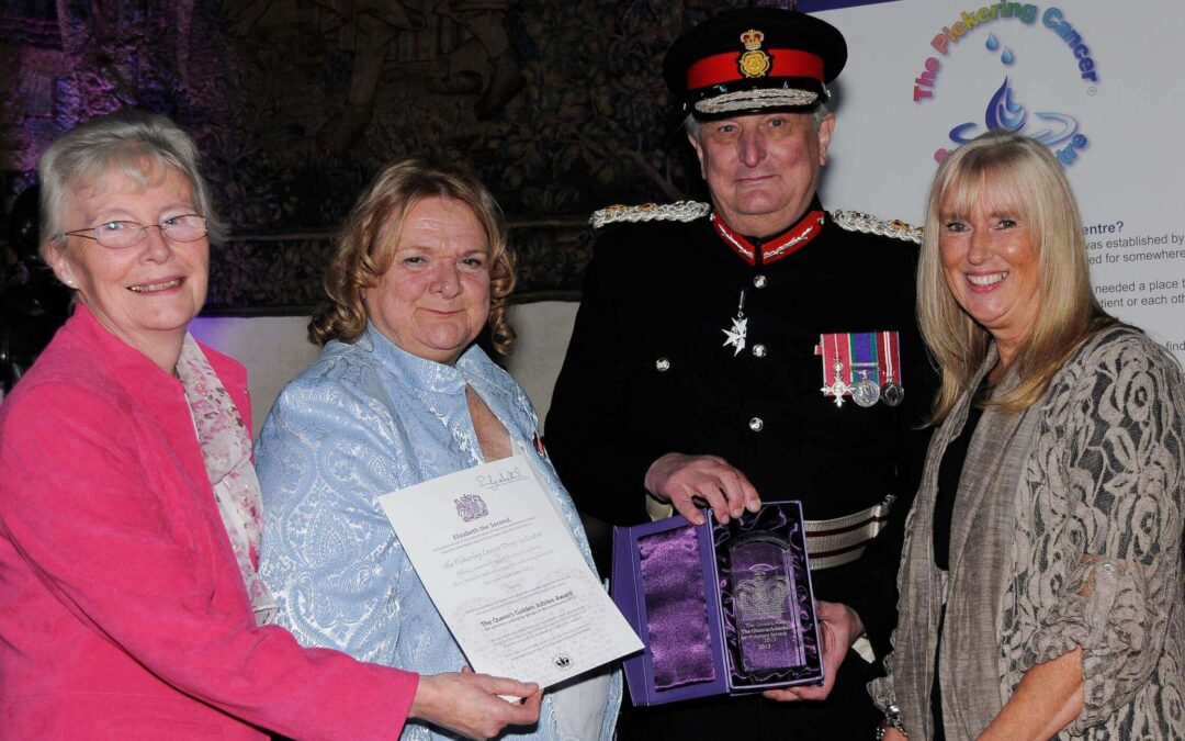 The Lord-Lieutenant presenting the QAVS crystal trophy to colleagues from The Pickering Centre
