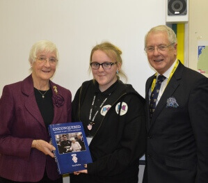 Ann West DL, pictured left, presenting a copy of 'Unconquered' to the Head Girl at Walderslade School, and pictured right is Cllr Mike O Brien. (c) Dr Fraser Campbell.